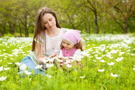 Happy mother and daughter among white flowers photo