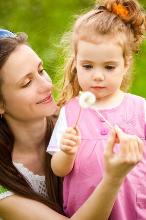 Mother and curly toddler girl with dandelions Stock Photo - 8013271