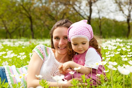 Sweet curly girl and her mother in the meadow photo