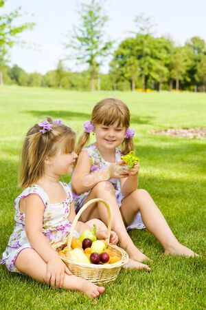 Two preschool sisters sitting in garden and playing with bubbles photo