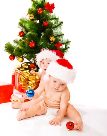 Two babies beside Christmas tree photo