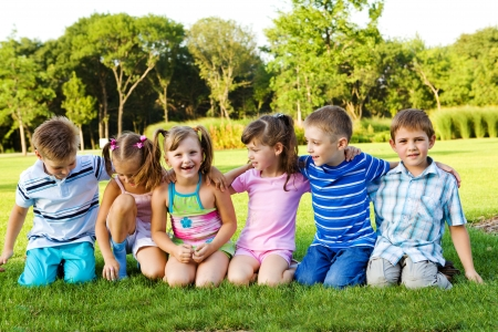 Little boys and girls sitting on grass and embracing photo