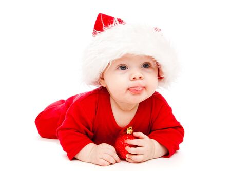 holding a christmas ornament: Baby in Santa hat with Christmas decoration Stock Photo