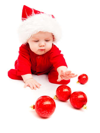 Baby in red costume playing with Christmas decoration photo