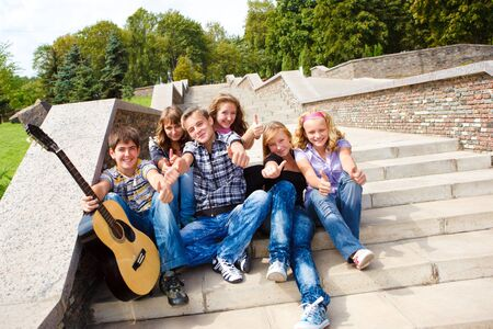 Group of young successful people showing thumbs up photo