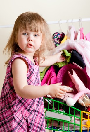 Cute blond girl placing  new dresses into shopping cart photo