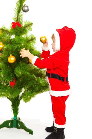 Baby in santa costume decorating Christmas tree photo