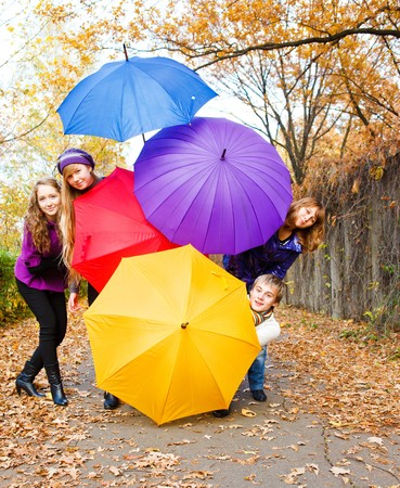 Teenage friends hiding behind umbrellas photo