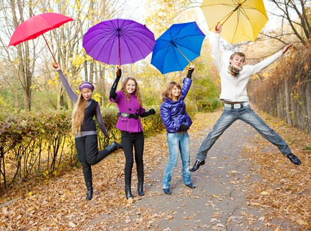 freetime: Teens jumping with umbrellas in hands