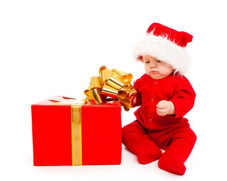 Baby in red clothing and Santa hat busy packing Christmas present photo