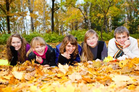 freetime: Friends on autumn leaves, laughing
