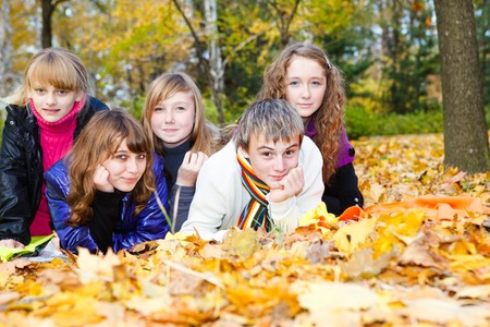 Group of joyful teens lying on autumnal leaves photo