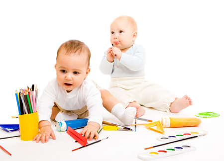 Smart toddlers with paints and paintbrushes photo