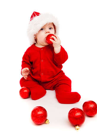 Gorgeous baby playing with red Christmas balls photo