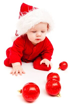 Sweetheart in red bodysuit and Santa hat looking at Christmas decoration photo
