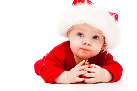 Kid holding red Christmas decoration in hands photo