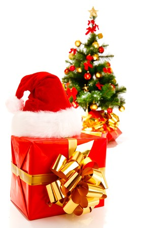 A present boxes wraped in red paper and Christmas tree behind photo