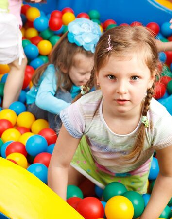 Cheerful preschoolers in a pool with colorful balls photo