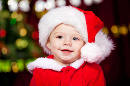 Portrait of a cheerful baby boy in Santa hat  photo