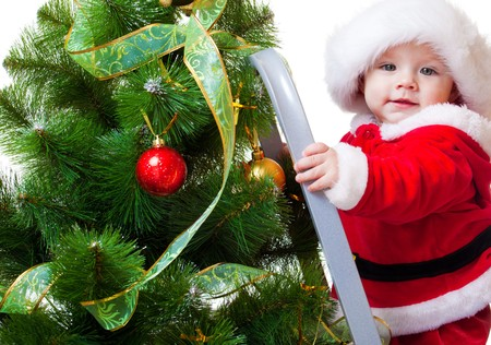 Baby in Santa costume standing on a step ladder and decorating Christmas tree photo