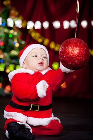 Baby in Santa costume playing with huge Christmas ball photo