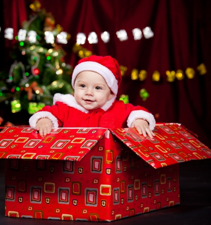 baby christmas: Excited kid in a present box Stock Photo