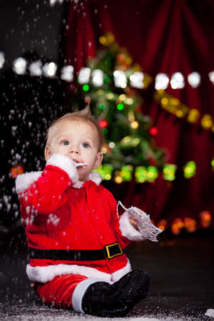 Sweet baby playing with snowflakes and looking at snow falling photo