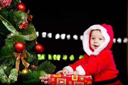 Baby in Santa costume on the black background photo