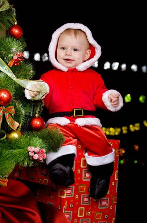 Cheerful baby boy sitting on the present box beside Christmas tree photo