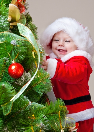 Baby decorating Christmas tree, over gray photo