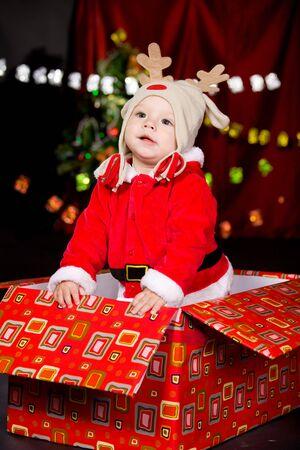 Attractive baby in Santa costume and deer hat photo