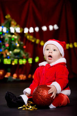 Surprised toddler having large Christmas ball in hands photo