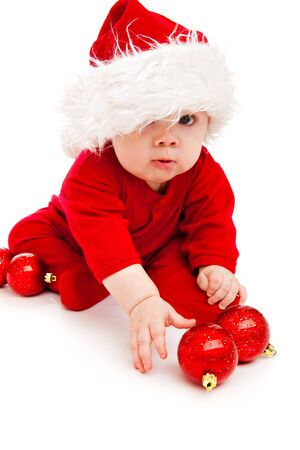 Funny baby in Santa hat and red bodysuit playing with Christmas balls photo