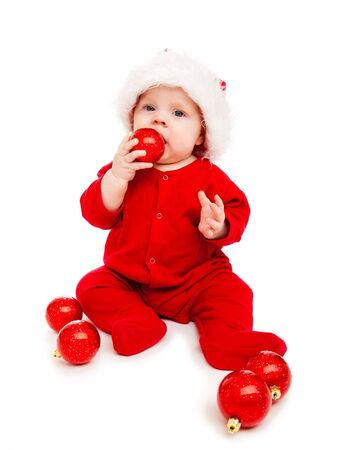 Beautiful baby Santa playing with red Christmas balls photo