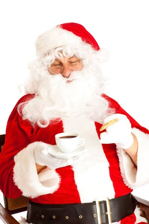 Santa Clause holding coffee cup and cookies in hands photo