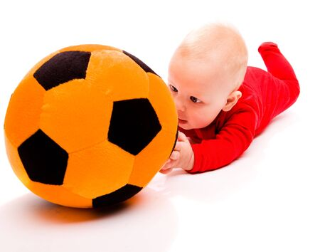 Surprised baby trying to get to the toy soccer ball photo