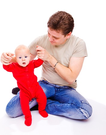 Father helping baby in red bodysuit to make his first steps photo