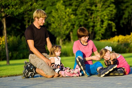 Cheerful parents and kids in roller skates photo