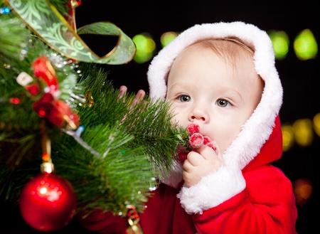 크리스마스 트리 옆에 산타 아기의 초상화 스톡 콘텐츠