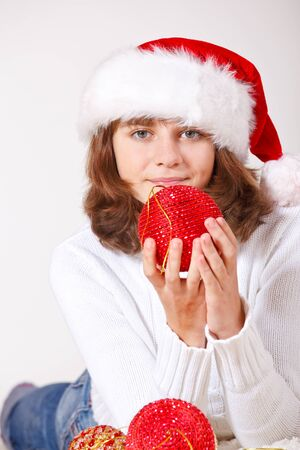 Teenage girl holding a red Christmas ball in hands photo