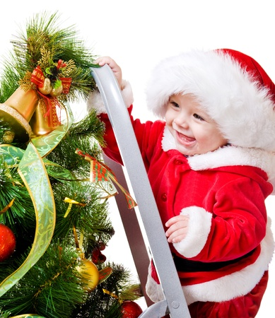 Baby decorating Christmas tree, isolated photo