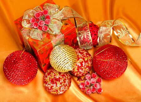 Christmas present with several red and golden balls over silk photo