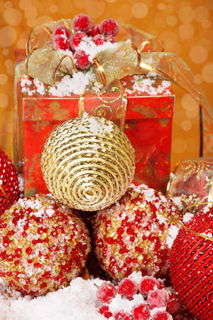 Several golden and red Christmas balls and a present, covered with snow photo