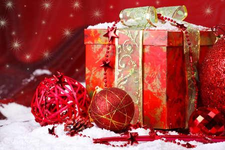 Present box and Christmas balls over red photo