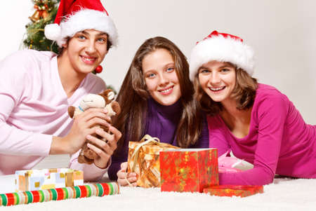 Three teenagers packing Christmas gifts photo