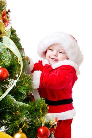 Baby standing on a step ladder and decorating Christmas tree photo