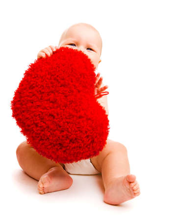 Cute happy valentine baby hiding behind fluffy heart photo