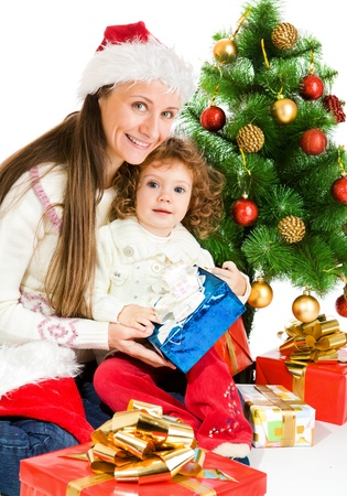 Woman and toddler girl sitting beside Christmas tree  photo