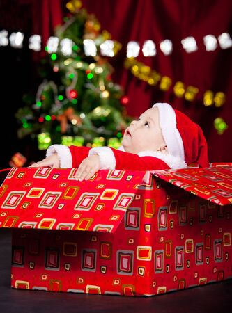 Baby in Christmas costume sitting in a large present box and looking up Stock Photo