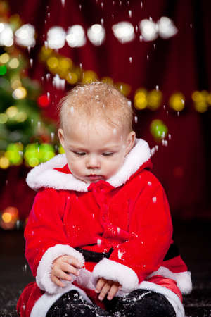 Baby in Santa costume playing with the snow falling photo